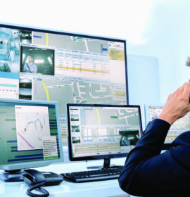 Security System Operator Looking At Cctv Footage While Talking On Telephone