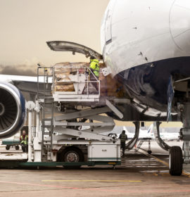 Loading cargo on the plane in airport, view through window